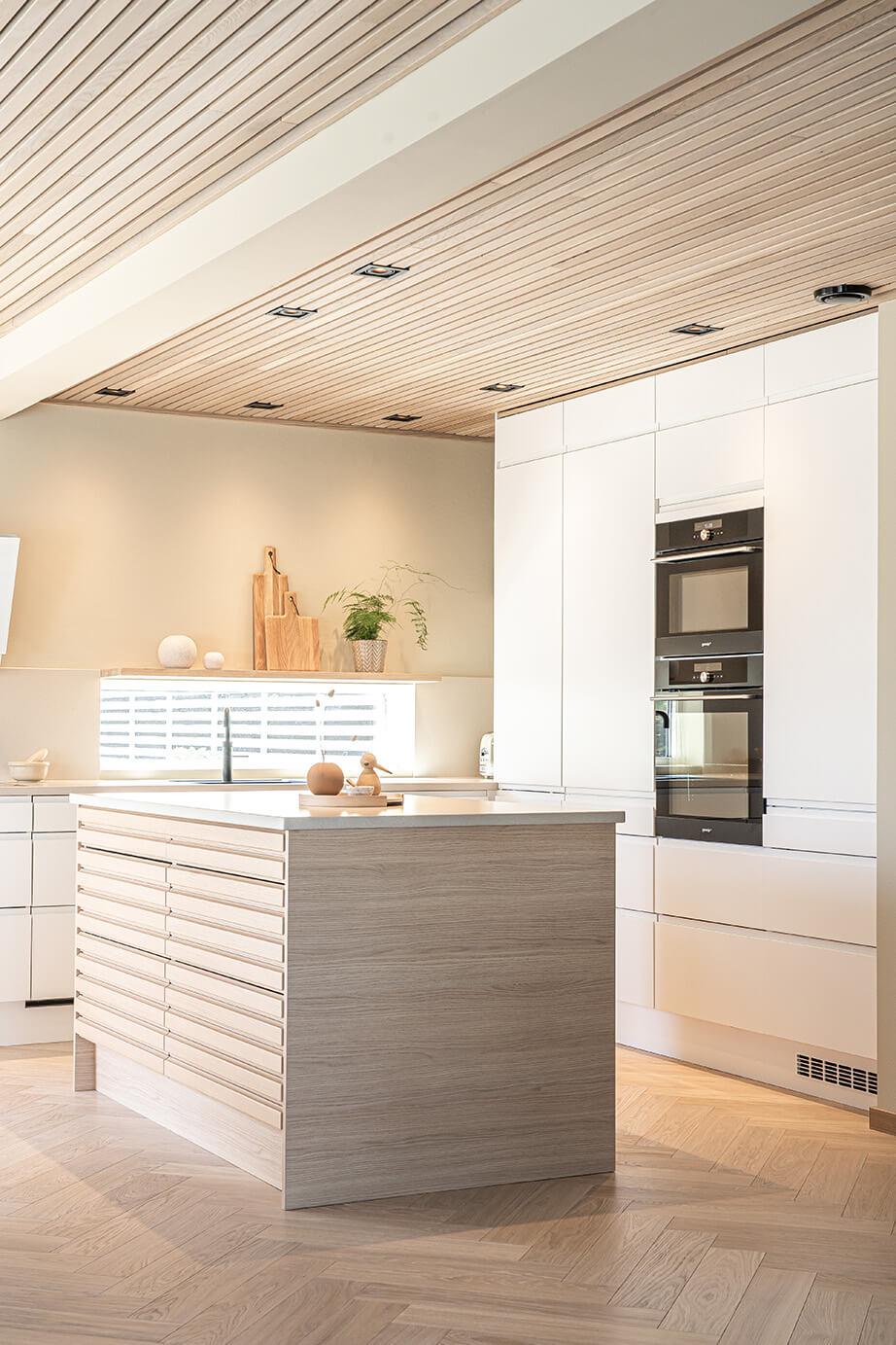 Lyst og lekkert kjøkken med kjøkkenøy i eikespiler, mot høyskapsvegg i hvite Mandalsfronter.