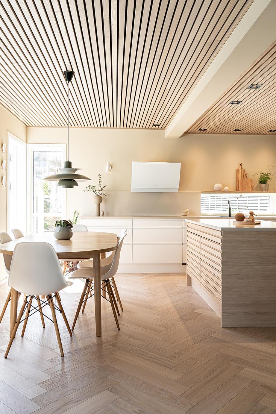 Hvitt kjøkken med sandfarget benkeplate i stein.