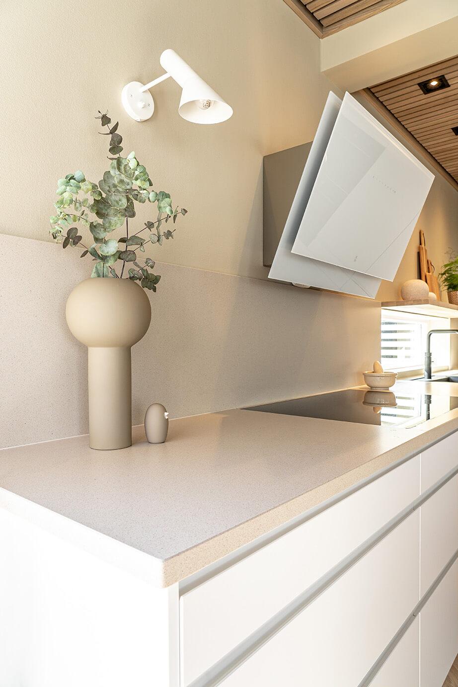 Nærbilde av benkeplate i sandfarget stein, mot hvite kjøkkenfronter